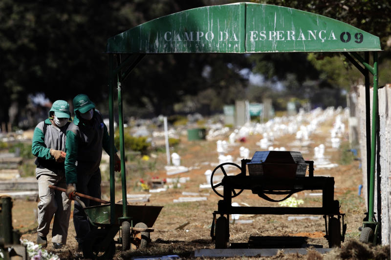 Cemetery workers prepare for the burial of Jose Mario de Souza Veiga, 83, whose family says died of COVID-19, at the Campo da Esperanca cemetery on the border of the neighborhoods of Taguatinga and Ceilandia, in Brasilia, Brazil, Tuesday, July 21, 2020. (AP Photo/Eraldo Peres)