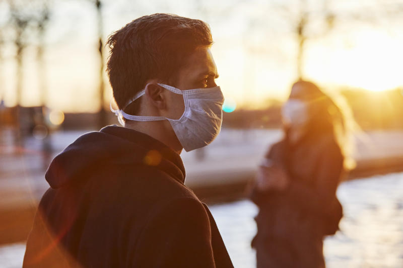 Young man and young woman in urban environment using protective face masks