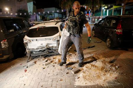 An Israeli policeman surveys the scene where a rocket exploded in the southern city of Sderot, Israel  August 8, 2018. REUTERS/Amir Cohen