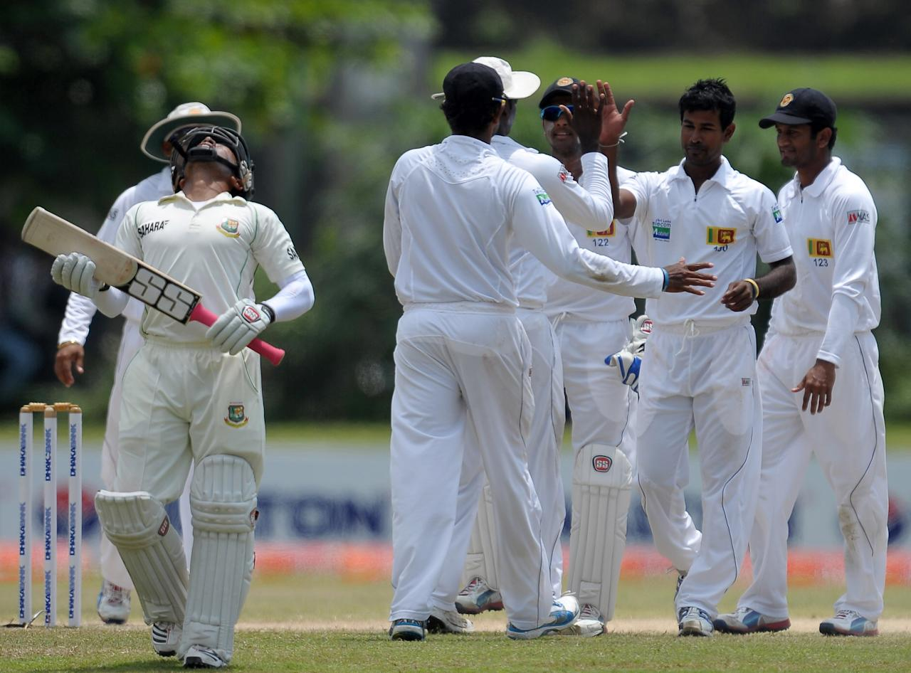 Sri Lankan cricketer Nuwan Kulasekara (2R) celebrates with teammates after he dismissed Bangladeshi captain Mushfiqur Rahim (L) for 200 during the fourth day of the opening Test match between Sri Lanka and Bangladesh at the Galle International Cricket Stadium in Galle on March 11, 2013.  AFP PHOTO/ LAKRUWAN WANNIARACHCHI        (Photo credit should read LAKRUWAN WANNIARACHCHI/AFP/Getty Images)