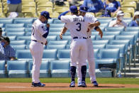 Los Angeles Dodgers shortstop Corey Seager, right, is hugged by Chris Taylor (3) next to manager Dave Roberts, left, after their team's World Series Championship ring ceremony before a baseball game against the Washington Nationals, Friday, April 9, 2021, in Los Angeles. (AP Photo/Marcio Jose Sanchez)