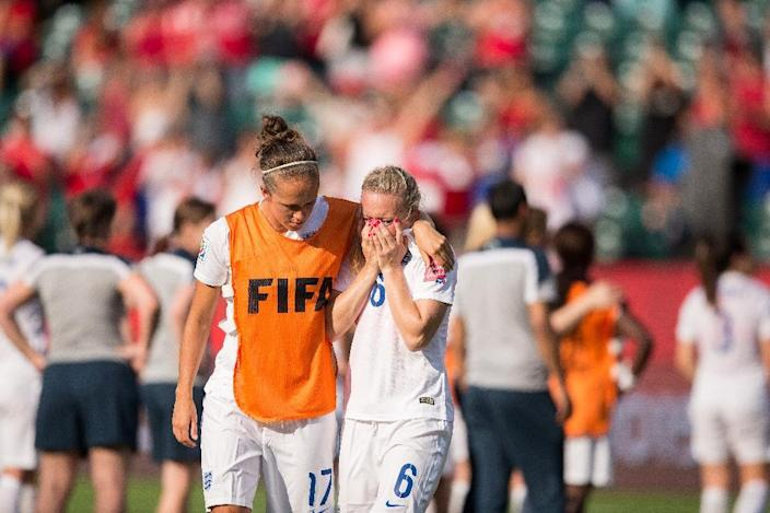 England's Jo Potter (L) consoles teammate Laura Bassett after she scored an own-goal in the last minutes of the game giving Japan the win in their semifinal match at the FIFA Women's World Cup in Edmonton, Canada on July 1, 2015 (AFP Photo/Geoff Robins)