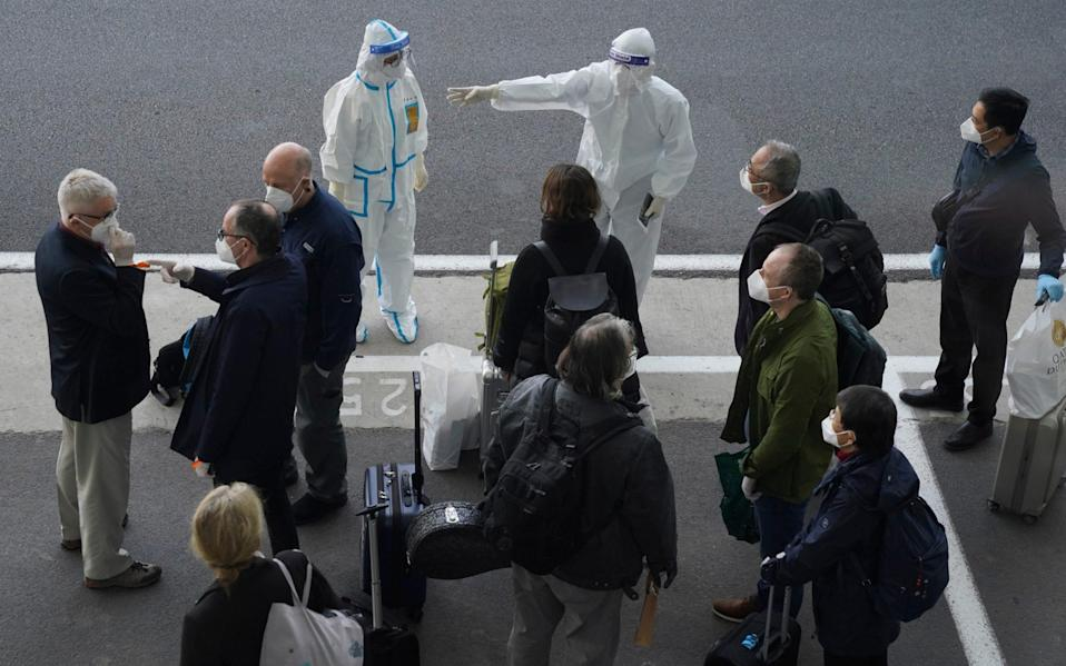 A worker in protective coverings directs members of the World Health Organization (WHO) - Ng Han Guan/AP