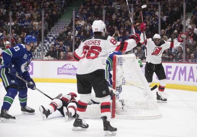 New Jersey Devils' Wayne Simmonds, back right, and Jack Hughes (86) celebrate Simmonds' goal against the Vancouver Canucks during the first period of an NHL hockey game in Vancouver, British Columbia, Sunday, Nov. 10, 2019. (Darryl Dyck/The Canadian Press via AP)
