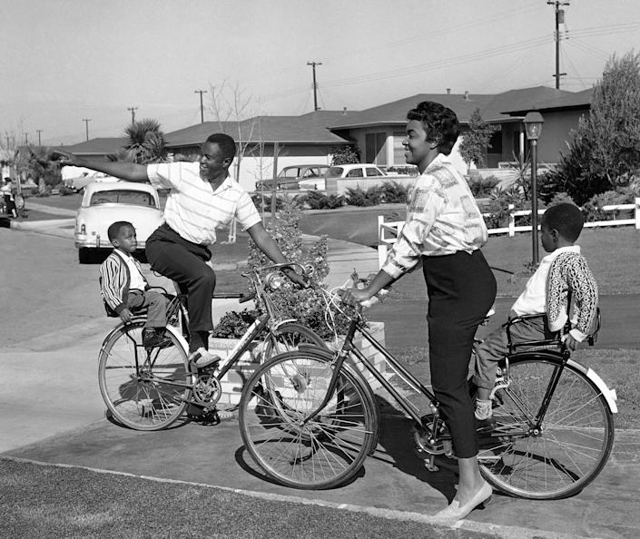 FILE - In this Wednesday, Dec. 12, 1962 file photo, Kenneth Kelly, an electrical engineer studying for his master's degree, points out his all-white neighborhood to his wife, Loretta, and sons David, 4, left, and Ronnie in Gardena, Calif. Kenneth C. Kelly, a Black electronics engineer whose antenna designs contributed to the race to the moon, made satellite TV and radio possible and helped NASA communicate with Mars rovers and search for extraterrestrials, has died. The 92-year-old also worked to erase race barriers in the Navy, in California housing and on the newspaper comics pages. Kelly had Parkinson's disease before his death on Feb. 27, 2021 his son Ron Kelly said. (AP Photo/David F. Smith, File)