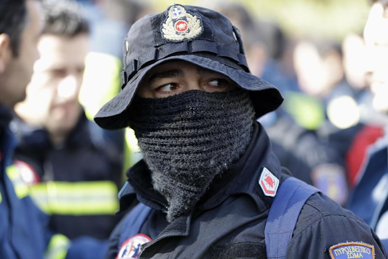 A firefighter cover his face with a scarf during a protest outside the parliament amid a contract dispute with the cash-trapped government, in Athens, Thursday, Feb. 16, 2017. The government says it is lacking the funds needed to offer thousands of firefighters long-term contracts. Greece is under pressure to make deeper spending cuts as it struggles to reach agreement with bailout lenders on the terms of future loan payouts. (AP Photo/Thanassis Stavrakis)