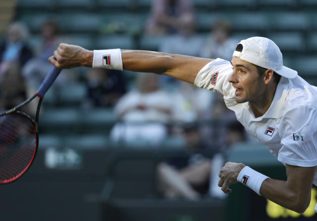 John Isner of the United States returns the ball to Canada's Milos Raonic during their men's quarterfinals match at the Wimbledon Tennis Championships, in London, Wednesday July 11, 2018. (AP Photo/Ben Curtis)