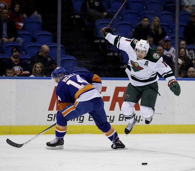 Minnesota Wild's Zach Parise, right, jumps over New York Islanders' Thomas Hickey's leg during the first period of the NHL hockey game, Tuesday, March 18, 2014, in Uniondale, New York. (AP Photo/Seth Wenig)