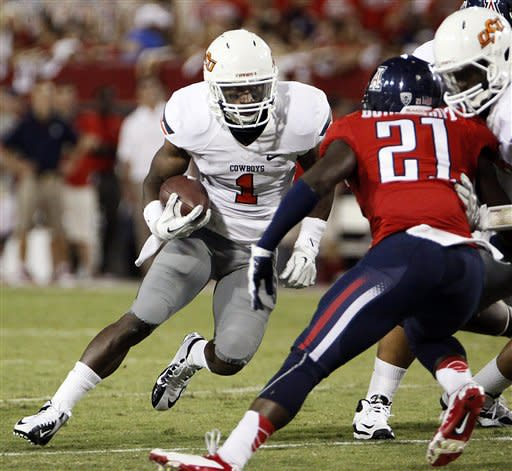 Oklahoma State running back Joseph Randle (1) tries to run around Arizona safety Tra'Mayne Bondurant (21) during the first half of an NCAA college football game at Arizona Stadium in Tucson, Ariz., Saturday, Sept. 8, 2012. (AP Photo/Wily Low)