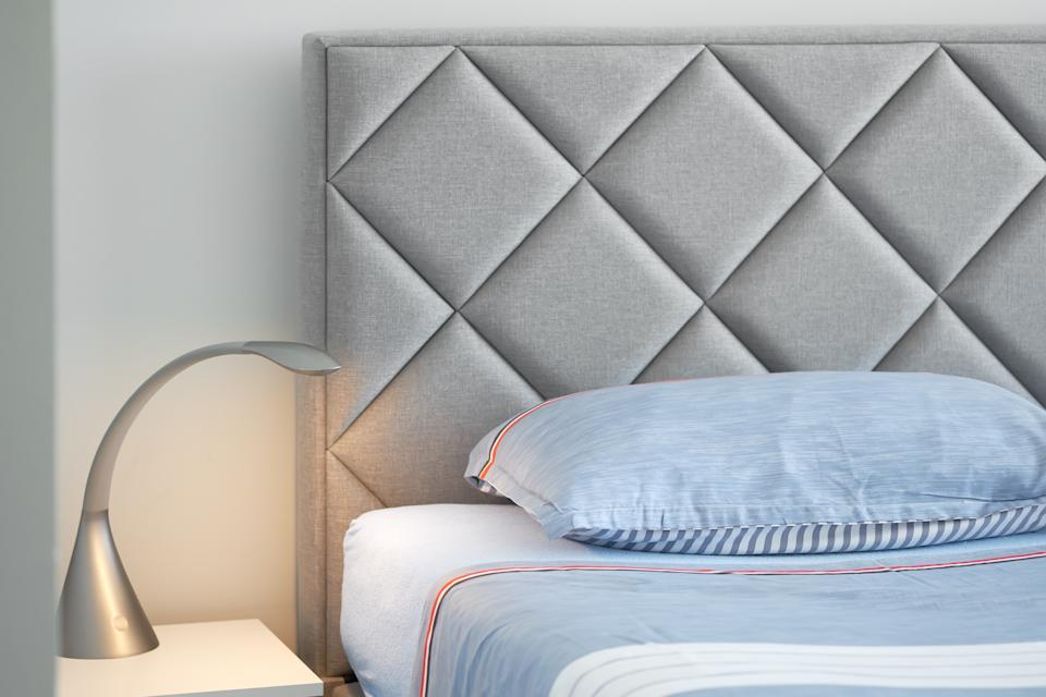 Silver colored lamp turned on in bedside table, part of bed with comfortable grey headboard, blue colour linens pillow cushion and sheet, no people, close up image, concept of resting, elegant details modern new home, vacations and holidays