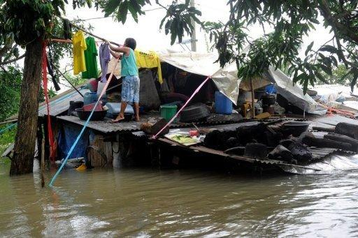 A woman hangs her washing on the roof of her submerged house in Pulilan, north of Manila. The Philippines deployed helicopters, inflatable boats and amphibious vehicles Sunday in a desperate bid to evacuate tens of thousands in the aftermath of successive monster storms