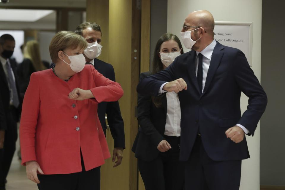 European Council President Charles Michel, right, greets German Chancellor Angela Merkel, left, with an elbow bump during a round table meeting at an EU summit in Brussels, Friday, July 17, 2020. Leaders from 27 European Union nations meet face-to-face on Friday for the first time since February, despite the dangers of the coronavirus pandemic, to assess an overall budget and recovery package spread over seven years estimated at some 1.75 trillion to 1.85 trillion euros. (Stephanie Lecocq, Pool Photo via AP)