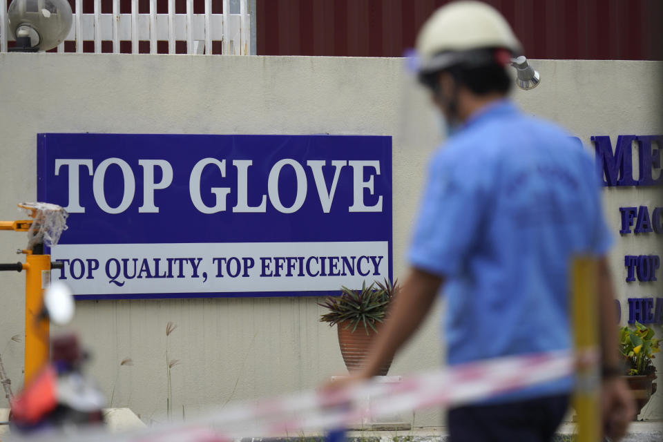 Workers from Top Glove walk outside Top Glove factory in Shah Alam, Malaysia, Wednesday, Nov. 25, 2020. Malaysia's Top Glove Corp., the world's largest maker of rubber gloves, says it expects delays in deliveries after more than 2,000 workers at its factories were infected by the coronavirus, raising the possibility of supply disruptions during the pandemic. (AP Photo/Vincent Thian)