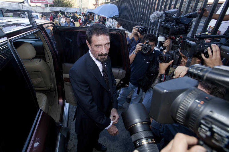 """Software company founder John McAfee poses for pictures after a press conference outside the Supreme Court in Guatemala City, Tuesday, Dec. 4, 2012. A Guatemalan official says McAfee, who has been identified as a """"person of interest"""" in the killing of his neighbor in Belize, 52-year-old Gregory Faull, was arrested on Wednesday, Dec. 5, 2012 in Guatemala City for entering the country illegally. (AP Photo/Moises Castillo)"""