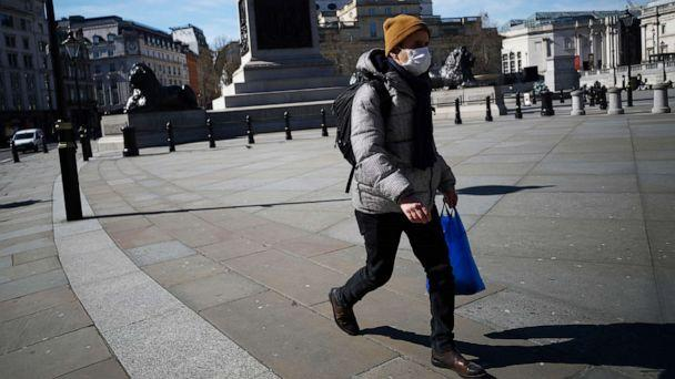 PHOTO: A man wears a mask in Trafalgar Square as the spread of the coronavirus continues, in London, March 23, 2020.  (Hannah Mckay/Reuters)