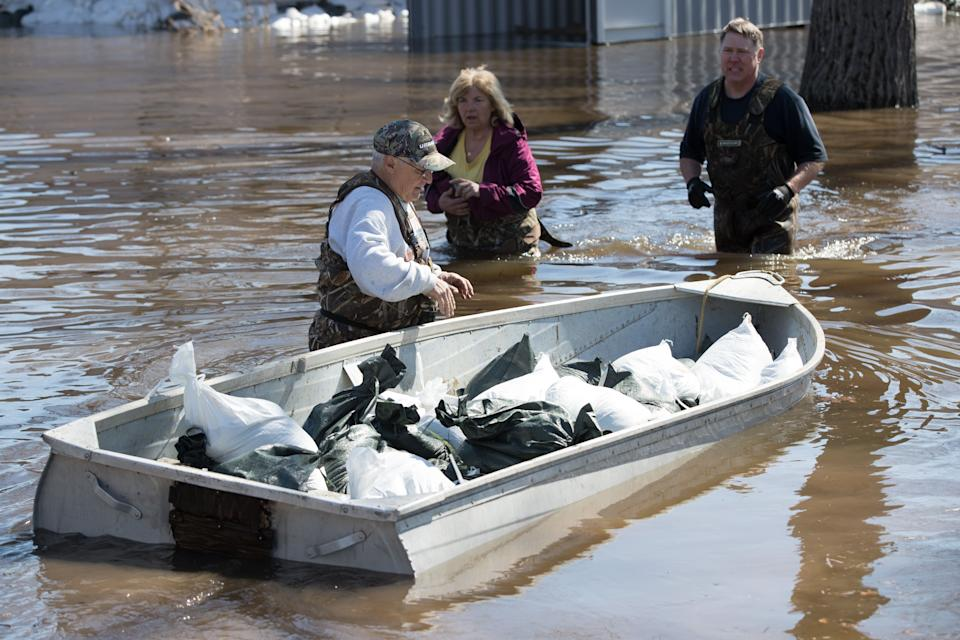 A man moves a boat full of sandbags to help with the flooding in Constance Bay, west of Ottawa, Ontario, on April 28, 2019. - More than 5,000 people were told to quickly leave their homes near Montreal late Saturday and early Sunday after floodwaters breached a dike in rain-soaked eastern Canada. According to the latest government data, nearly 8,000 people have been forced by rising waters from their homes in Quebec, and about 6,000 homes have been flooded -- topping the 2017 toll during what was then the area's worst flooding in a half-century. ast week, both Montreal and the capital Ottawa declared states of emergency. In Fredericton, New Brunswick, crews have been busy hauling away driftwood and debris as waters start to recede. (Photo by Lars Hagberg / AFP)        (Photo credit should read LARS HAGBERG/AFP via Getty Images)