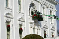 A worker hangs holiday wreaths on the White House on Saturday, Nov. 21, 2020, in Washington. (AP Photo/Jacquelyn Martin)