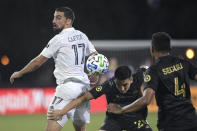 LA Galaxy midfielder Sebastian Lletget (17) competes for the ball with Los Angeles FC midfielder Eduard Atuesta (20) and defender Eddie Segura (4) during the first half of an MLS soccer match Saturday, July 18, 2020, in Kissimmee, Fla. (AP Photo/Phelan M. Ebenhack)
