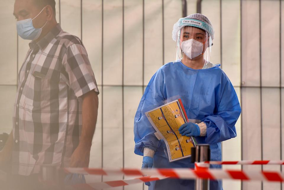 A healthcare worker is stationed at a swab test site in a public housing estate after a nearby food centre became a coronavirus disease (COVID-19) cluster, in Singapore, June 16, 2021. REUTERS/Caroline Chia