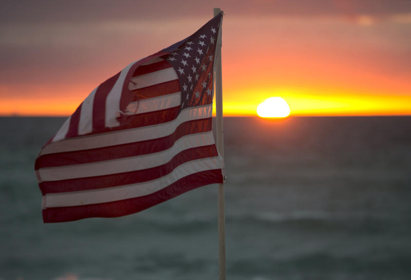 An American flag flutters in the breeze as the sun rises on Hollywood Beach, Tuesday, Feb. 2, 2016, in Hollywood, Fla. (AP Photo/Wilfredo Lee)