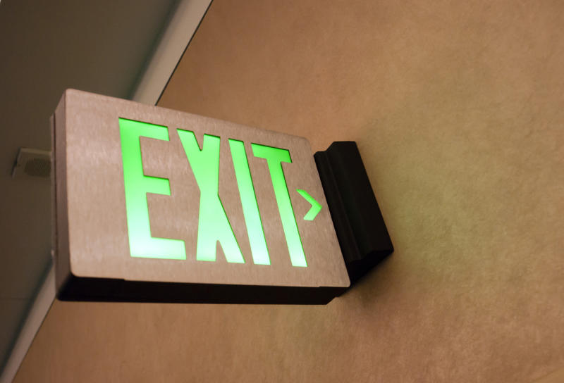 An illuminated emergency exit sign over a door.