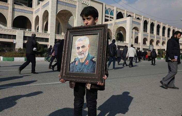 A boy carries a portrait of Iranian Revolutionary Guard Gen. Qassem Soleimani, who was killed by a U.S. airstrike in Iraq, prior to the Friday prayers in Tehran, Iran, on January 3, 2020. Hundreds of thousands of mourners took to the streets across Iran to pay their respects to a figure who was widely hailed as a war hero in Iran.