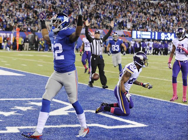 New York Giants wide receiver Rueben Randle (82) celebrates after catching a pass for a touchdown as Minnesota Vikings cornerback Chris Cook (20) and Mistral Raymond (41) react during the first half of an NFL football game Monday, Oct. 21, 2013 in East Rutherford, N.J. (AP Photo/Bill Kostroun)