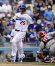 Los Angeles Dodgers' David Freese, left, scores on a sacrifice fly by Chris Taylor as Philadelphia Phillies catcher J.T. Realmuto, right, reaches for a tag during the eighth inning of a baseball game Sunday, June 2, 2019, in Los Angeles. (AP Photo/Mark J. Terrill)
