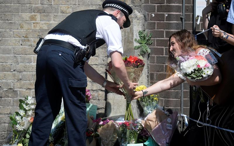 A police officer helps a woman leave flowers near the scene - Credit: HANNAH MCKAY/REUTERS