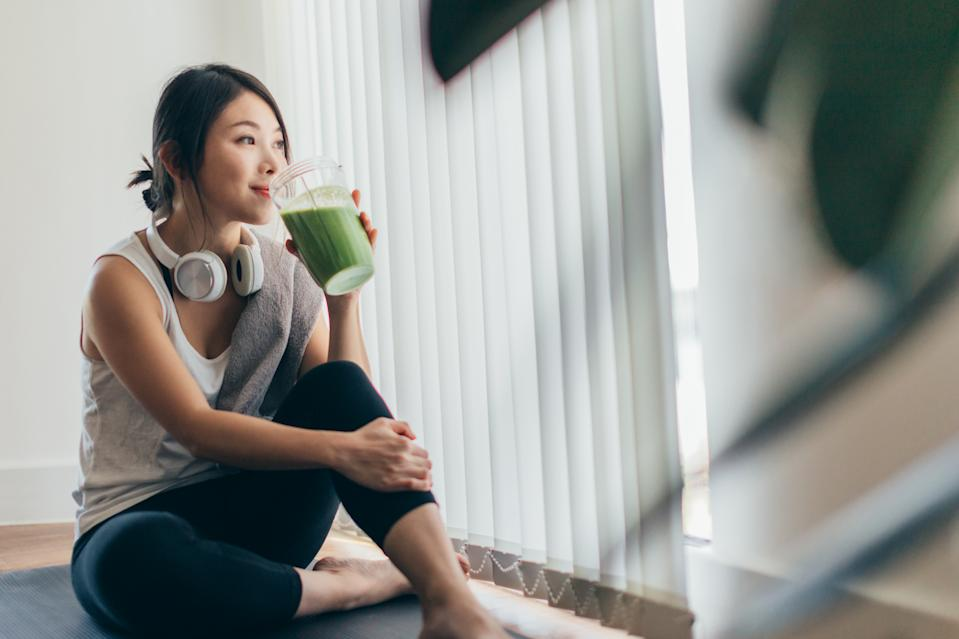 Beautiful young Asian woman in sportswear drinking protein shake after exercise, relaxing at home.