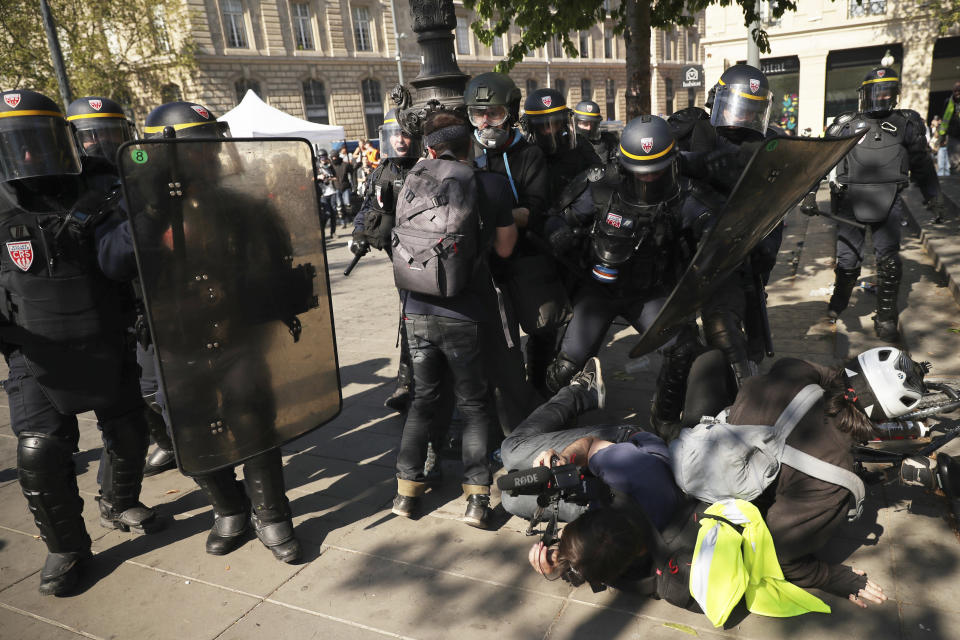 Police confront protestors and a photographer during a yellow vest demonstration in Paris, Saturday, April 20, 2019. French yellow vest protesters are marching anew to remind the government that rebuilding the fire-ravaged Notre Dame Cathedral isn't the only problem the nation needs to solve. (AP Photo/Francisco Seco)