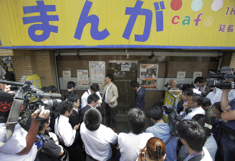 "Journalists stand in front of a comic book cafe where Katsuya Takahashi, a former Aum Shinrikyo cult member, was detained by police, in Tokyo Friday, July 15, 2012. Police arrested Takahashi, 54, the last fugitive suspected in the doomsday cult's deadly nerve gas attack on Tokyo subways 17 years ago, on suspicion of murder. Japanese characters on the cafe read: ""Manga, or comic."" (AP Photo/Itsuo Inouye)"