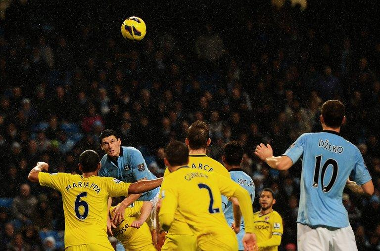 Manchester City's Gareth Barry (2nd L) climbs onto Reading's Nicky Shorey to score the winning goal on December 22, 2012