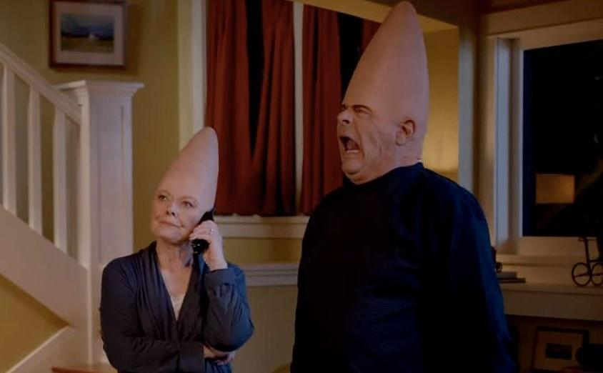 """The """"coneheads"""", Mary Margaret and Donald stand in their living room, Mary Margaret is on the phone while Donald pulls a face."""
