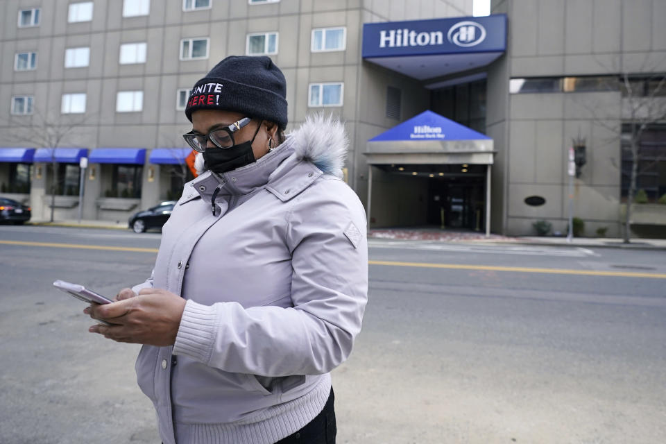 Hotel housekeeper Esther Montanez looks at her cell phone outside the Hilton Back Bay, Friday, March 5, 2021, in Boston. Montanez refuses to give up hope of returning to her cleaning job at the hotel, which she held for six years until being furloughed since March 2020 due to the COVID-19 virus outbreak. The single mother cannot bear the idea of searching for work that will almost certainly mean earning near the minimum wage. (AP Photo/Charles Krupa)