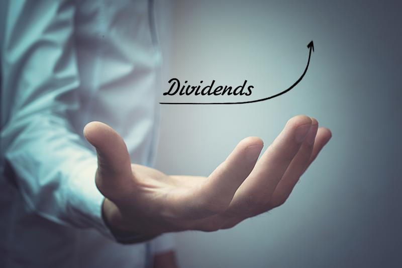 """A person holding out their hand with the word """"dividends"""" above and an arrow sloping upward."""