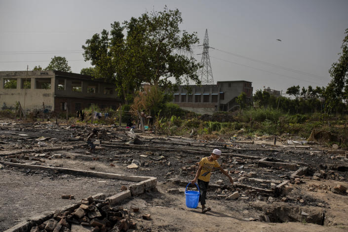 A young Rohingya refugee boy carries a bucket of water through the charred remains of the slum they lived in earlier near a refugee camp alongside the banks of the Yamuna River in the south-eastern borders of New Delhi, sprawling Indian capital, July 1, 2021. Millions of refugees living in crowded camps are waiting for their COVID-19 vaccines. For months, the World Health Organization urged countries to prioritize immunizing refugees, placing them in the second priority group for at-risk people, alongside those with serious health conditions. (AP Photo/Altaf Qadri)