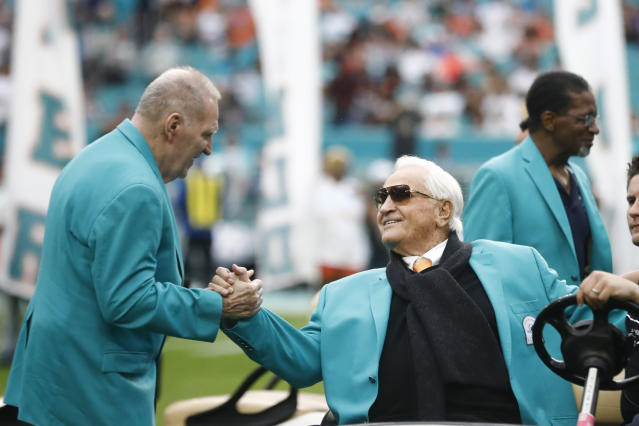FILE - In this Dec. 22, 2019, file photo, former Miami Dolphins head coach Don Shula, right, is greeted on the field by former players during half time at an NFL football game against the Cincinnati Bengals in Miami Gardens, Fla. Shula, who won the most games of any NFL coach and led the Miami Dolphins to the only perfect season in league history, died Monday, May 4, 2020, at his South Florida home, the team said. He was 90. (AP Photo/Brynn Anderson, File)