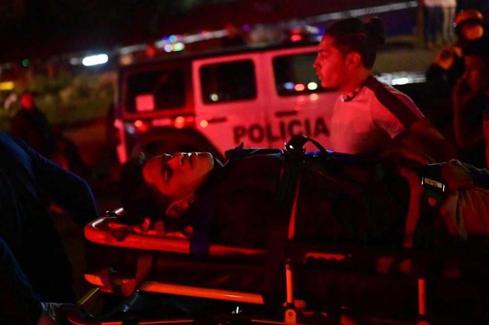 An injured person on a stretcher bathed in red light at night.