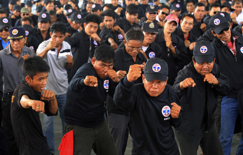"""In this April 3, 2014 photo, black-clad supporters of Thai Prime Minister Yingluck Shinawatra punch imaginary opponents during training in Udon Thani province, Thailand. Following the directions of a trainer on a nearby stage, they fended off kicks and practiced footwork to loud speakers blaring music typically heard at a Thai kickboxing stadium. It was was part of a two-day training course for farmers, laborers and others in the heart of pro-government """"Red Shirt"""" country - Thailand's rural, poor north and northeast. (AP Photo/Sakchai Lalit)"""