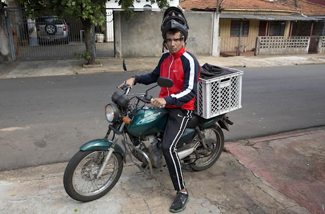 """In this May 29, 2014 photo, soccer player Rogerio Salvato Jr. poses for a portrait on his motorcycle prior to making a delivery for a restaurant in Presidente Prudente, Brazil. """"I wouldn't be able to provide for my family only by playing football,"""" he said. """"... I make more money by delivering takeout than I do by playing football."""" (AP Photo/Andre Penner)"""