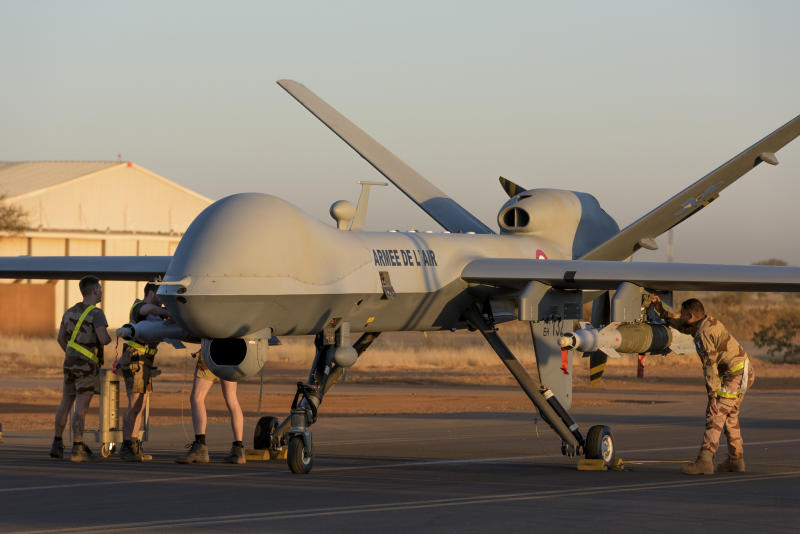 This photo provided by the French Defense Ministry communication center and taken Tuesday Dec. 17, 2019, shows French soldiers loading a French Reaper drone with two GBU 12 missiles on Niamey airbase, Niger. France's defense ministry said Monday that it had carried out its first armed drone strike, killing seven Islamic extremists in central Mali over the weekend. France joins a tiny group of countries that use armed drones, including the United States. (Malaury Buis/EMA/DICOD via AP)