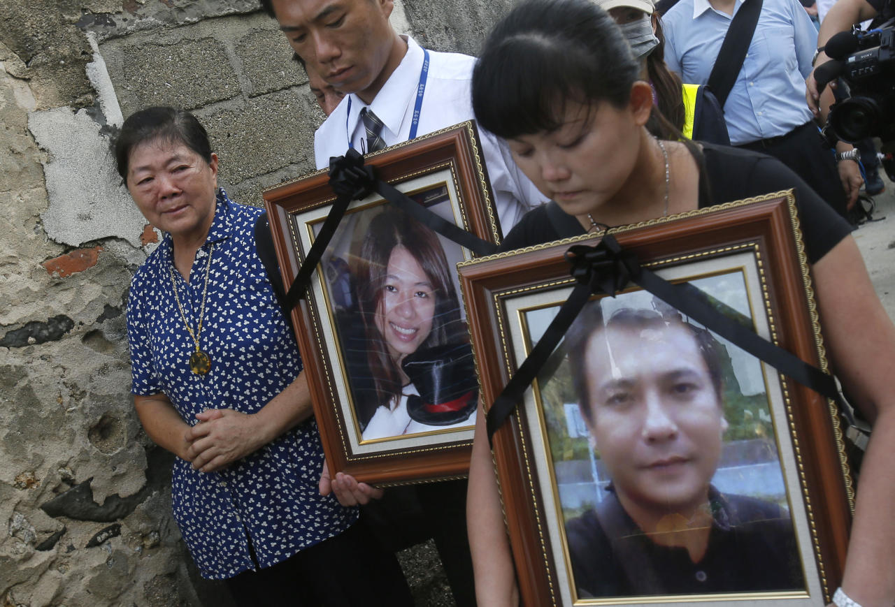 Relatives of victims killed in the TransAsia Airways Flight GE222 crash pray with the victims' portraits during a makeshift ceremony at the crash site on the outlying island of Penghu, Taiwan, Thursday, July 24, 2014. Stormy weather on the trailing edge of Typhoon Matmo was the likely cause of the plane crash that killed more than 40 people, the airline said Thursday. (AP Photo/Wally Santana)