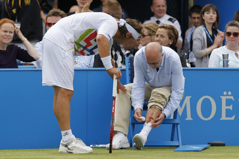 Argentina's David Nalbandian, left, checks on the line judge after causing an injury to him, for which he was disqualified, during the Queen's Club grass court championships final tennis match against Croatia's Marin Cilic, London, Sunday, June 17, 2012. Nalbandian kicked the small barrier surrounding the line judge in anger. A piece of the barrier then hit the line judge, causing bleeding on his left shin. (AP Photo/Sang Tan)