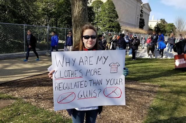 Emma, 14, holds her sign comparing the dress code regulation for high school girls versus gun regulations at the March for Our Lives in Washington, D.C. (Christopher Wilson/Yahoo News)