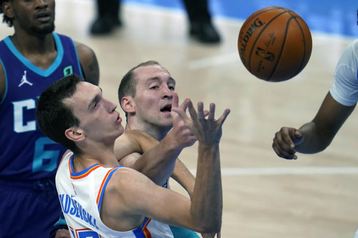 Oklahoma City Thunder forward Aleksej Pokusevski, left, and Charlotte Hornets center Cody Zeller, right, watch a rebound in the first half of an NBA basketball game Wednesday, April 7, 2021, in Oklahoma City. (AP Photo/Sue Ogrocki)