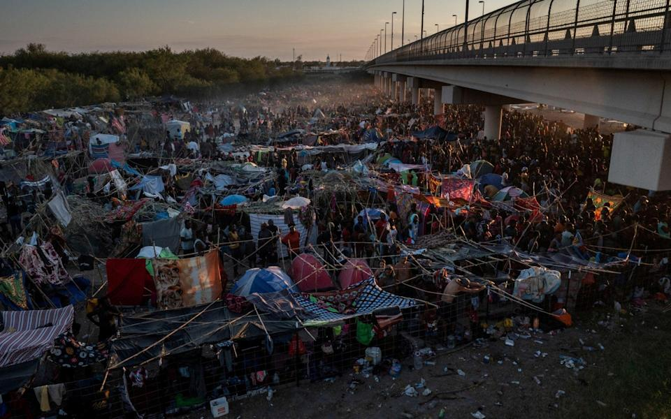 Migrants take shelter along the Del Rio International Bridge at sunset as they await to be processed after crossing the Rio Grande river - Reuters