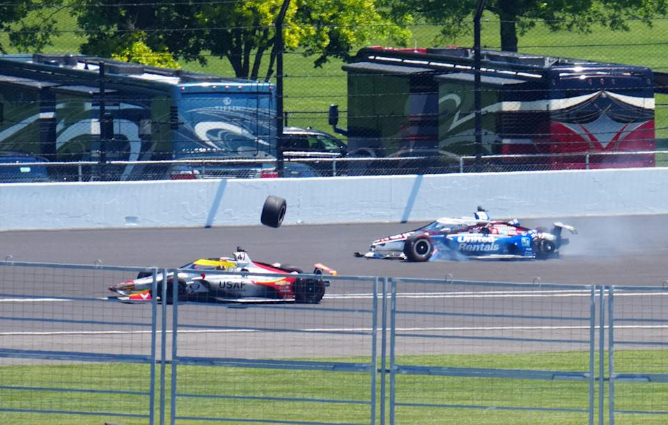 Conor Daly, left, hits the tire that flew off of Graham Rahal's car as Rahal spins during the 105th Indianapolis 500.