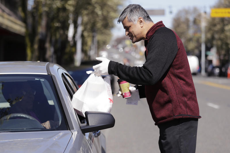 In this Tuesday, March 31, 2020, photo, Glen Quadros, owner of the Great American Diner & Bar, hands over a takeout food order, packaged in compostable containers placed inside a plastic bag, to a waiting customer in Seattle. Just weeks earlier, cities and even states across the U.S. were busy banning straws, limiting takeout containers and mandating that shoppers bring reusable bags or pay a small fee. Grocery clerks are nervous that the virus could linger on reusable fabric bags and their unions are backing them up with demands to end plastic bag fees and suspend bag bans. The plastics industry has seized the moment, lobbying to overturn existing bans on single-use plastics. (AP Photo/Elaine Thompson)
