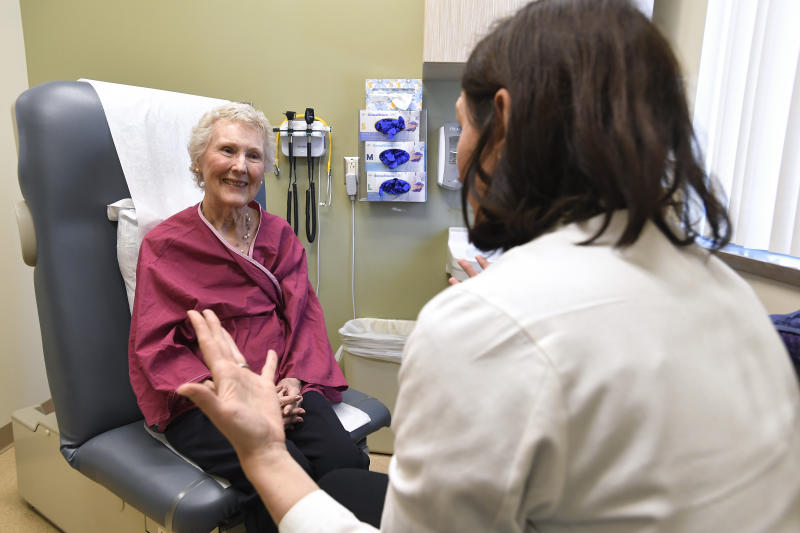 "In this Monday, March 4, 2019, Nancy Simpson, left, speaks with Dr. Allison Magnuson, Geriatric Oncology and Breast Oncology at Wilmot Cancer Institute, at the Pluta Cancer Center in Rochester, N.Y. Simpson, 80, says she ""wanted to do the maximum I could handle"" to fight her disease. (AP Photo/Adrian Kraus)"